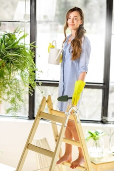 Portret van een jonge vrouwelijke tuinman die met een gieter op de ladder in de oranjerie staat