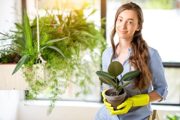 Portret van een jonge vrouwelijke tuinman met een bloempot in de oranjerie
