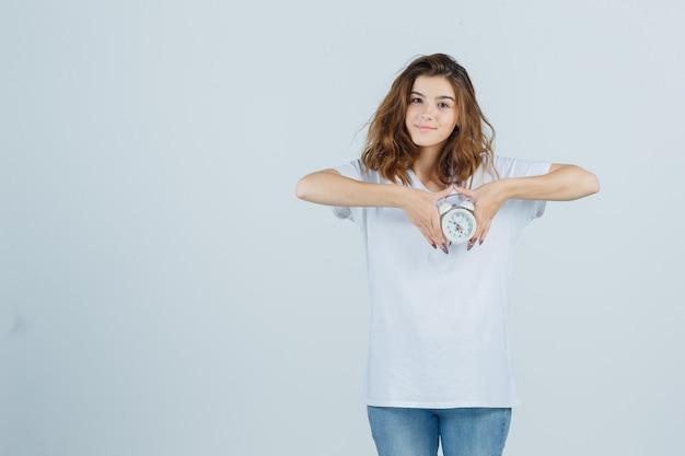 Portret van een jonge vrouwelijke wekker in wit t-shirt, spijkerbroek en op zoek vrolijk vooraanzicht