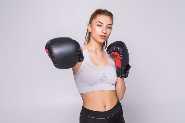 Portret van een jonge vrouwenbokser die een stoot aan voorzijde gooit tijdens het oefenen