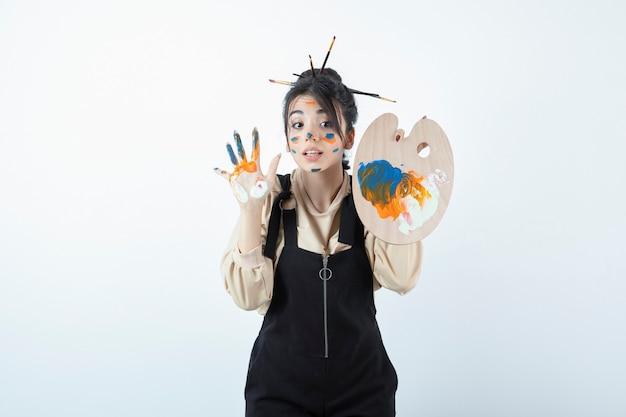 Portret van een jonge vrouwenkunstenaar die met een geschilderd gezicht stelt en houten palet houdt.