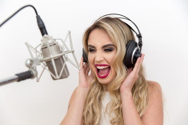 Portret van een jonge vrouwenzanger met hoofdtelefoons voor de microfoon.
