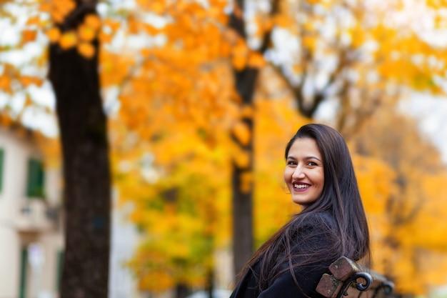 Portret van een jonge vrouwenzitting in de herfstpark