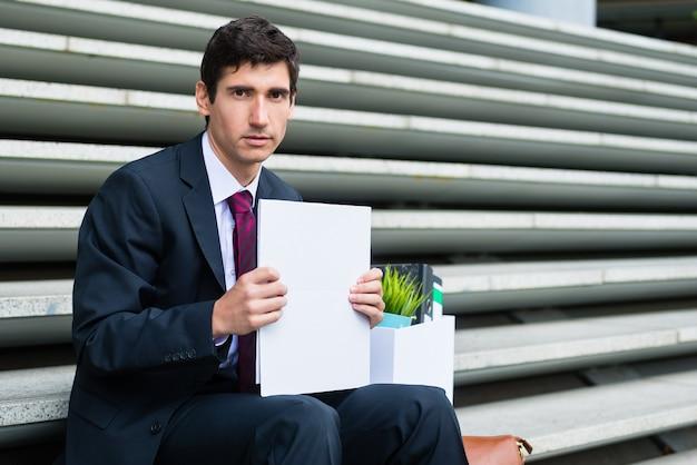 Portret van een jonge werkloze man camera kijken met droevige gezichtsuitdrukking zittend op de trap buiten na te zijn ontslagen