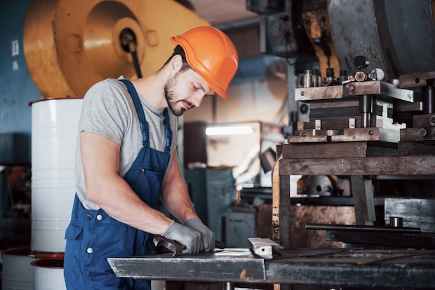 Portret van een jonge werknemer in een bouwvakker bij een grote afvalrecyclingfabriek.