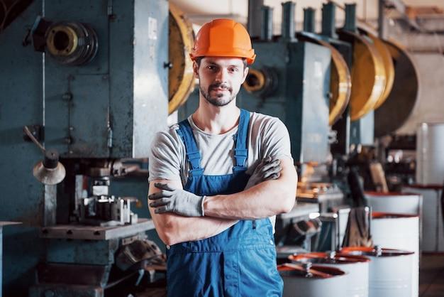 Portret van een jonge werknemer in een harde hoed bij een grote metaalbewerkingsfabriek.