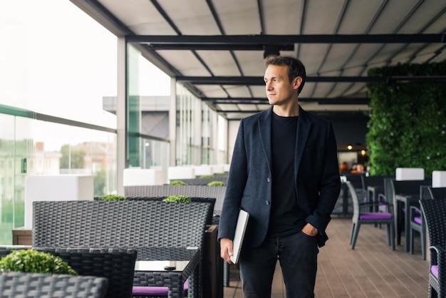 Portret van een jonge zakenman die een laptop vasthoudt die in café staat