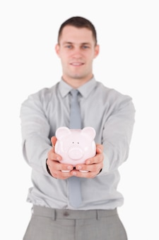 Portret van een jonge zakenman die een spaarvarken houdt