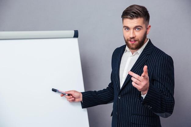 Portret van een jonge zakenman die in kostuum iets op een leeg bord over grijze muur presenteert