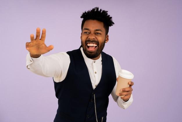 Portret van een jonge zakenman die lacht en hallo zegt tegen iemand met zijn hand tegen een geïsoleerde achtergrond. bedrijfsconcept.