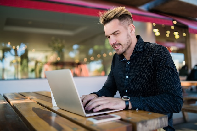 Portret van een jonge zakenman die op zijn laptop werkt terwijl hij in een coffeeshop zit