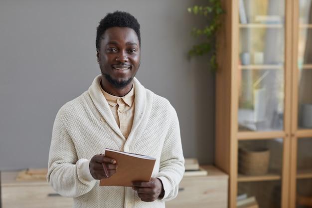Portret van een jonge zakenman in de witte map van de sweaterholding en glimlachen vooraan die zich op kantoor bevinden