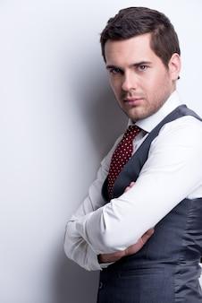Portret van een jonge zakenman in grijs pak met gekruiste armen vormt over muur met contrastschaduwen.