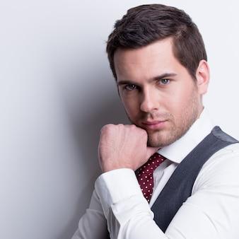 Portret van een jonge zakenman in grijs pak met hand in de buurt van gezicht vormt over muur.