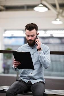 Portret van een jonge zakenman kijken naar klembord praten op mobiele telefoon