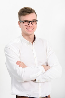 Portret van een jonge zakenman met gekruiste die wapens aan camera kijken tegen witte achtergrond wordt geïsoleerd