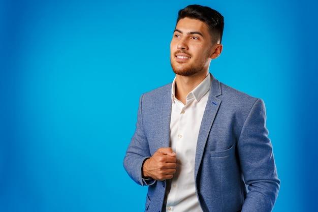 Portret van een jonge zakenman tegen blauw