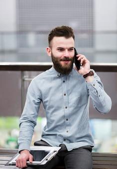 Portret van een jonge zakenman zittend op een bankje bedrijf klembord en digitale tablet praten op mobiele telefoon