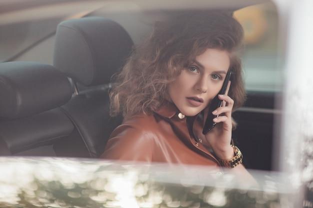 Portret van een jonge zakenvrouw die in de auto zit en met een smartphone spreekt