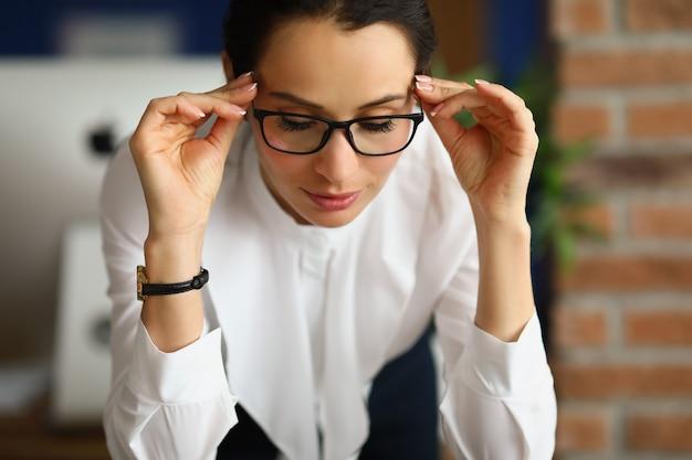 Portret van een jonge zakenvrouw die opstijgt en haar bril afzet