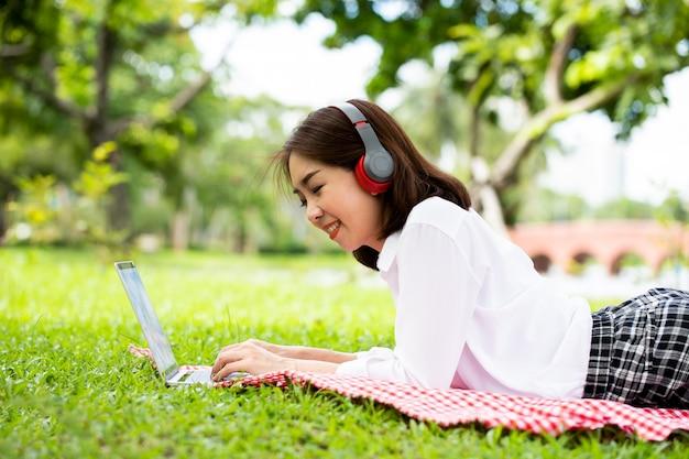 Portret van een jonge zakenvrouw draagt gezichtsmasker en gebruikt tablet in het park om te ontspannen na het werken
