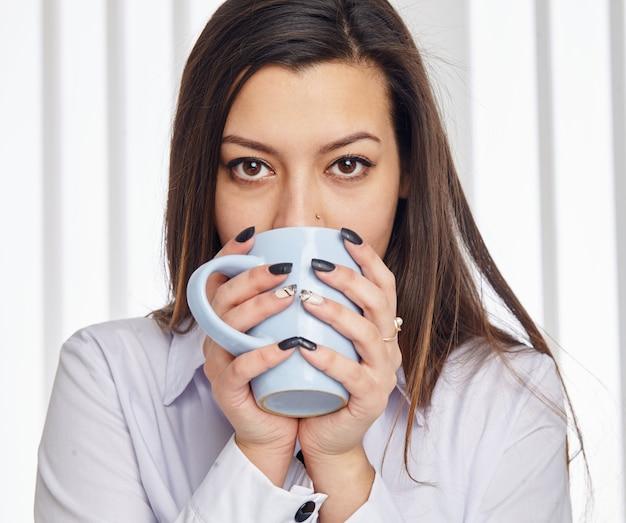Portret van een jonge zakenvrouw drinken van een kopje koffie, close-up, kijkend naar de camera.
