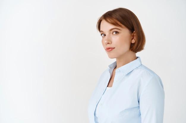 Portret van een jonge zakenvrouw in blouse met kort natuurlijk haar, kijkend en glimlachen, staande tegen een witte muur