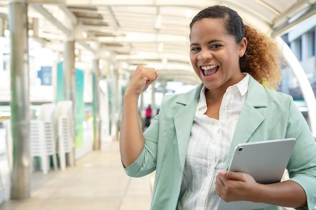 Portret van een jonge zakenvrouw manier om te werken op straat met tablet in de stad.