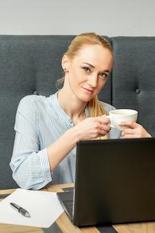 Portret van een jonge zakenvrouw met laptop zittend aan tafel met een kopje koffie in een café
