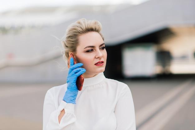 Portret van een jonge zakenvrouw met telefoon, laptop, tablet, koffie buitenshuis. blond meisje in rubber blauwe handschoenen.