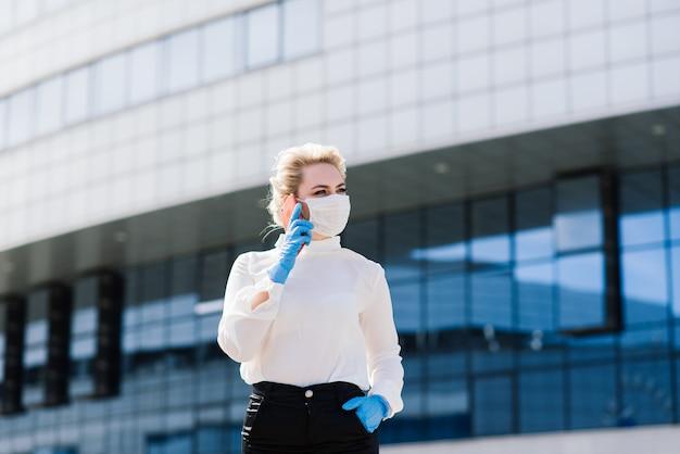 Portret van een jonge zakenvrouw met telefoon, laptop, tablet, koffie buitenshuis. blondemeisje in rubber blauwe handschoenen en masker.