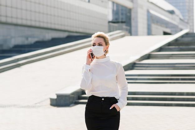Portret van een jonge zakenvrouw met telefoon, laptop, tablet, koffie buitenshuis. vrij blond meisje in rubber blauwe handschoenen en masker.