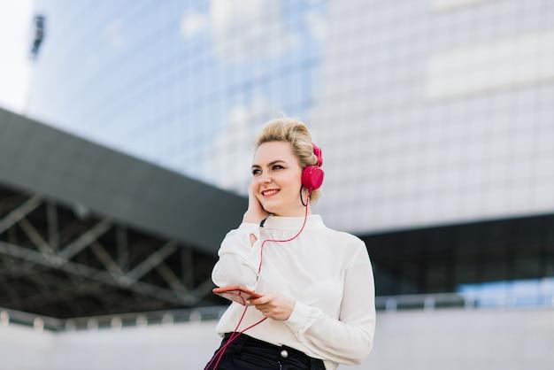 Portret van een jonge zakenvrouw met telefoon, laptop, tablet, koffie buitenshuis. vrij blond meisje in rubber blauwe handschoenen.