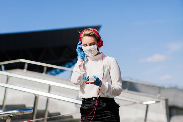 Portret van een jonge zakenvrouw met telefoon, notebook, tablet, koffie buitenshuis. blond meisje in rubberen blauwe handschoenen en masker.