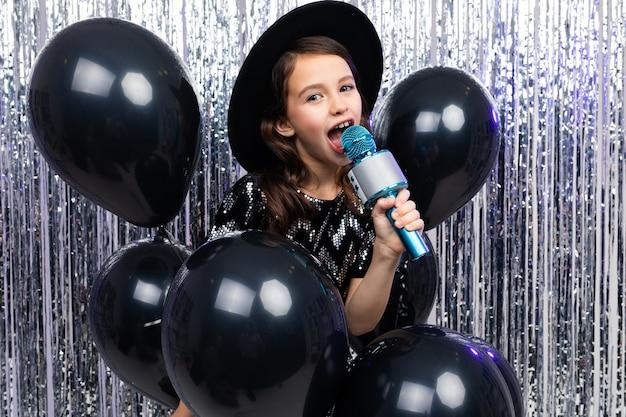 Portret van een jonge zangeres in een zwarte jurk met een microfoon in haar handen op een glanzende achtergrond.