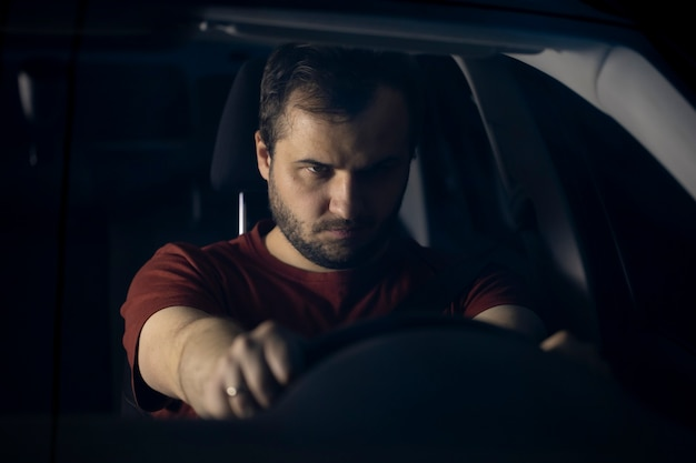Portret van een jonge zelfverzekerde bebaarde man die een stuurwiel met zijn handen geklemd