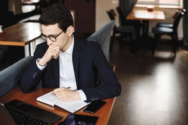 Portret van een jonge zelfverzekerde bedrijfsmens die terwijl het zitten van een ta-bureau werkt die zijn laptop bekijkt denken gekleed in kostuum dat een bril draagt.