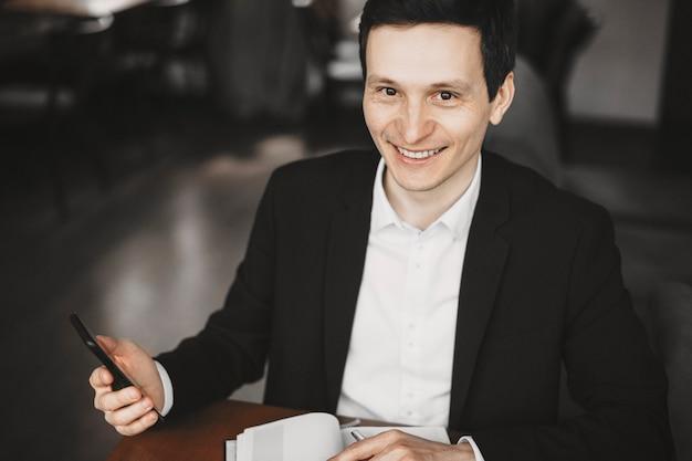 Portret van een jonge zelfverzekerde man aan zijn bureau met een smartphone en kijken naar camera glimlachen.