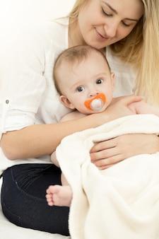 Portret van een jonge zorgzame moeder die op bed zit en de baby op handen houdt