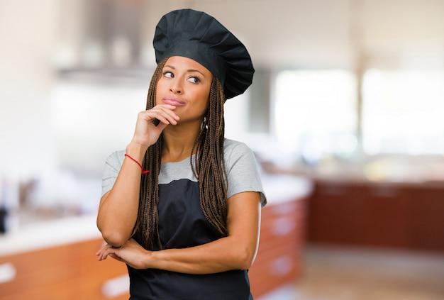 Portret van een jonge zwarte bakkersvrouw die denkt en omhoog kijkt, verward over een idee, zou een oplossing proberen te vinden