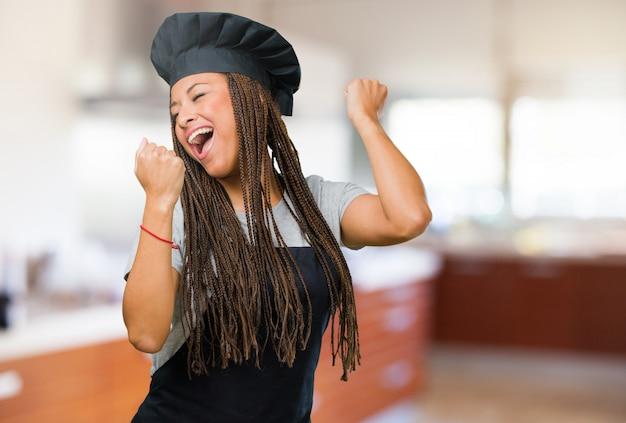 Portret van een jonge zwarte bakkersvrouw zeer gelukkig en opgewekt, die wapens opheffen