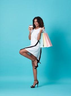 Portret van een jonge zwarte die creditcard en het winkelen zak toont