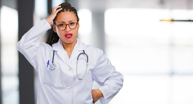 Portret van een jonge zwarte dokter vrouw bezorgd en overweldigd, vergeetachtig, iets realiseren, uitdrukking van shock op het hebben van een fout gemaakt