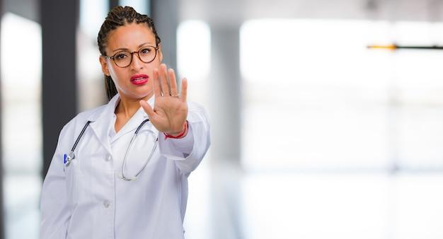 Portret van een jonge zwarte ernstige en bepaalde artsenvrouw