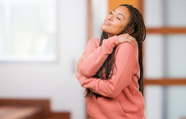 Portret van een jonge zwarte trots en zeker het dragen van vlechten, wijzende vingers, te volgen voorbeeld, concept tevredenheid, arrogantie en gezondheid