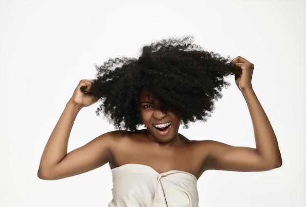 Portret van een jonge zwarte vrouw die lacht met bretels