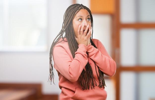 Portret van een jonge zwarte vrouw draagt vlechten erg bang en bang, wanhopig naar iets, huilt van lijden en open ogen, concept van waanzin