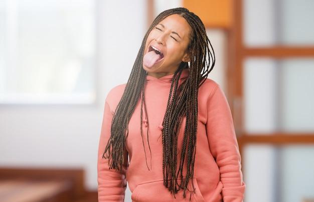 Portret van een jonge zwarte vrouw met vlechten uitdrukking van vertrouwen en emotie, plezier en vriendelijk, met tong als een teken van spel of plezier
