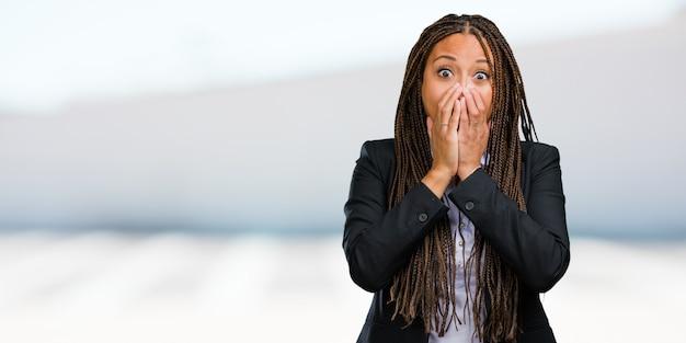 Portret van een jonge zwarte zakenvrouw erg bang en bang, wanhopig naar iets, schreeuwt van lijden en open ogen, concept van waanzin