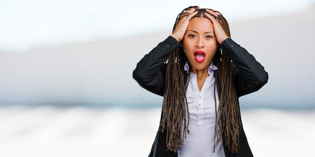 Portret van een jonge zwarte zakenvrouw gefrustreerd en wanhopig, boos en verdrietig met de handen op het hoofd